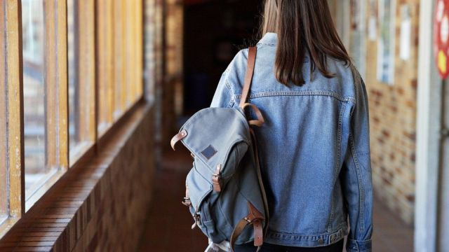 Girl walking down a school corridor