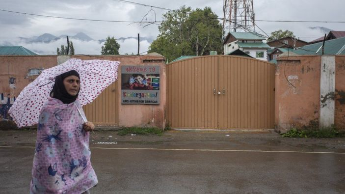 A woman walks in front of a shut primary school