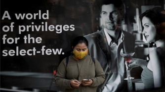 An Indian commuter wears a protective mask as she waits next to a vaccination center in Kolkata, India, 03 February 2021.