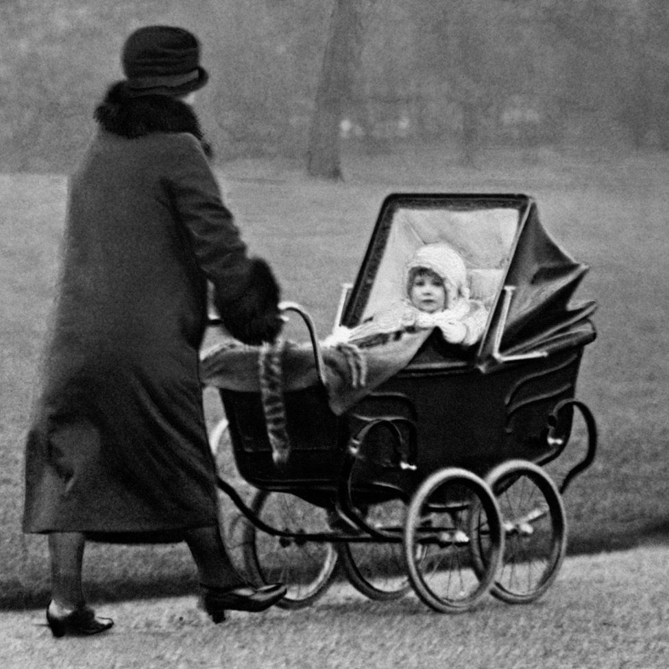 Princess Elizabeth being pushed in a pram in a park
