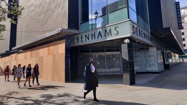 People walk by a closed Debenhams