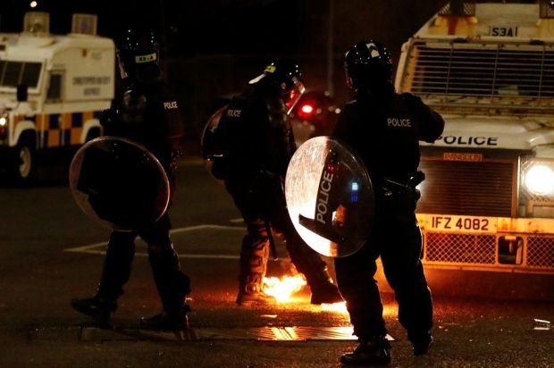 Police in riot gear watch as a petrol bomb lands close to them in Belfast