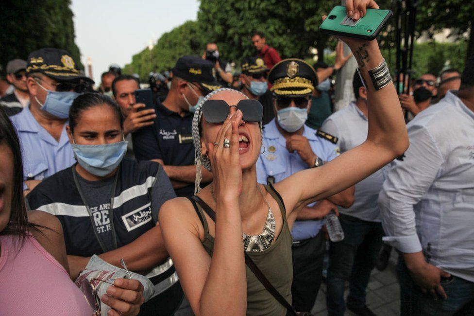 A woman is seen shouting at the front of a group of protesters in June 2021.
