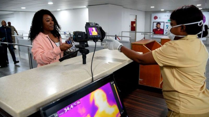 A Port Health Service staff member stands next to a thermal scanner as passengers arrive at the Murtala Mohammed International Airport in Lagos,