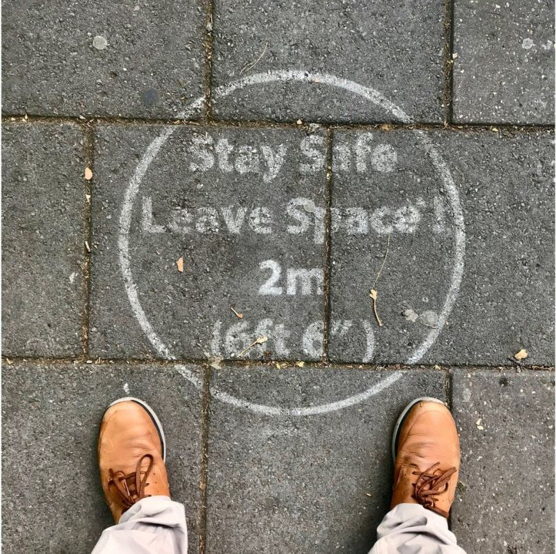 A stencil outline instructing people to maintain a two-metre distance