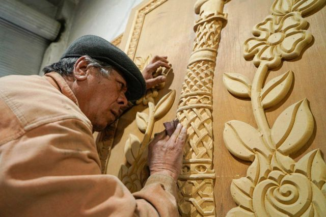 A man carves into a wooden door with great care.