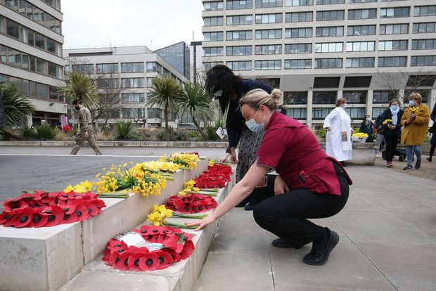 Members of staff place flowers outside St Thomas' Hospital