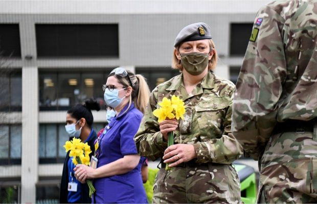 Military and NHS medical staff observe a minute of silence whilst holding daffodils