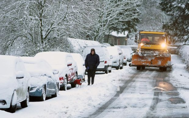 A man walks his dog through snow-covered roads in Allenheads, Northumberland, 21 January 2021