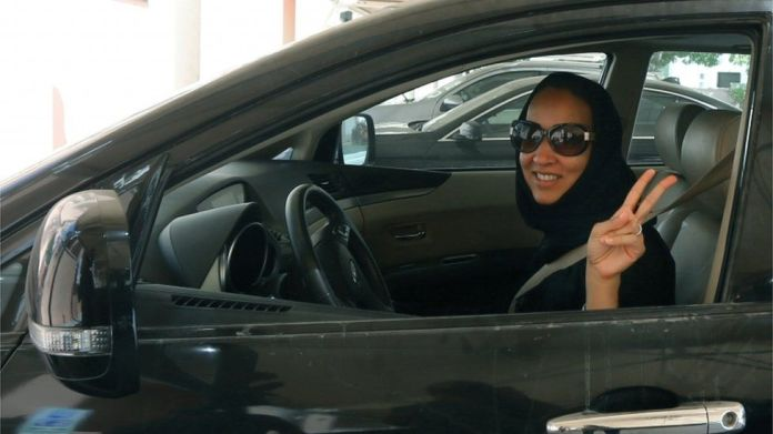 """Saudi Arabian activist Manal Al Sharif, who now lives in Dubai, flashes the sign for victory as she drives her car in the Gulf Emirate city on October 22, 2013, in solidarity with Saudi women preparing to take to the wheel on October 26, defying the Saudi authorities, to campaign women""""s right to drive in Saudi Arabia."""