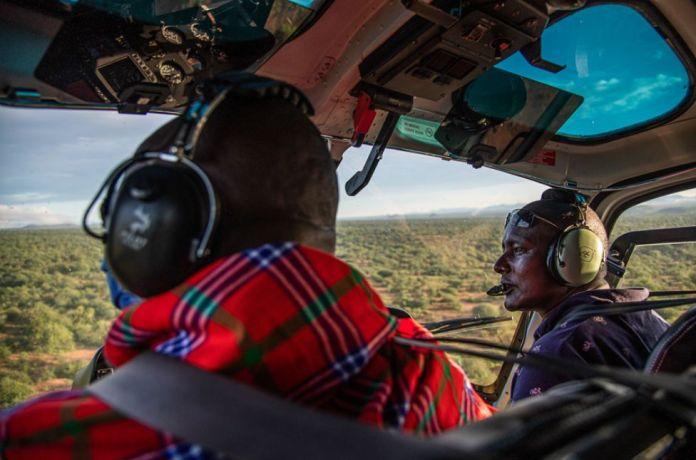 Ambrose Ngetich et le capitaine Iltasayon Neepe regardent depuis le cockpit d'un hélicoptère