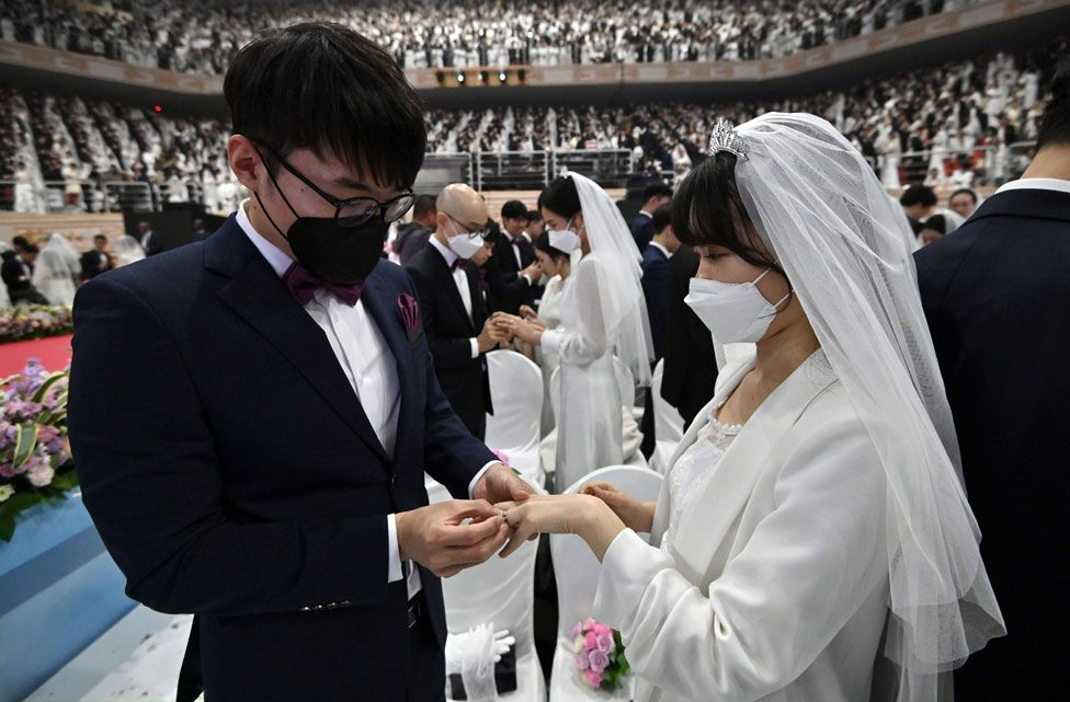 Couples exchange rings a mass wedding ceremony organised by the Unification Church in Gapyeong