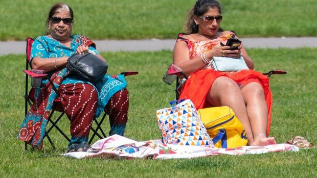 People picnic in the sun in Greenwich Park, London