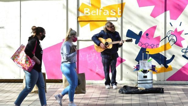 A busker performs as shoppers walk by in Belfast