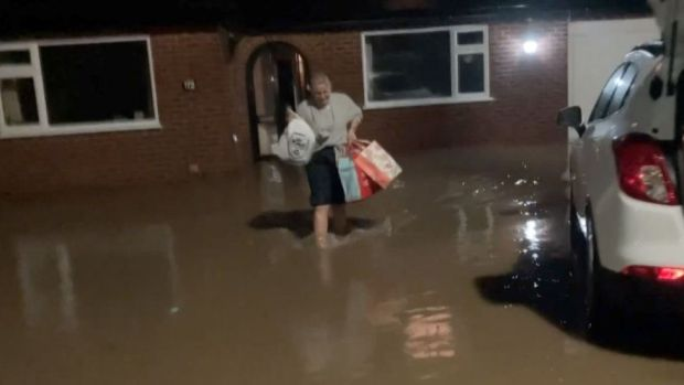 Woman carrying her belongings through flood water in Ruthin