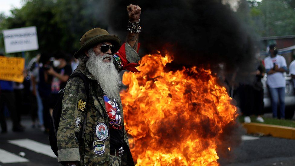 Protestor with raised hand and fire behind him