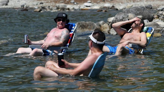Beachgoers sit in the water at Alouette Lake to cool off during the scorching weather of a heatwave in Maple Ridge, British Columbia