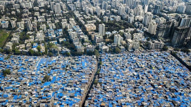 Prédios de um lado e casas com telhaod de lona azul para proteger das chuvas, em Mumbai, Índia