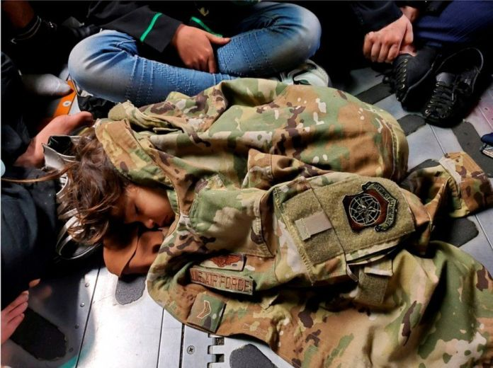 An Afghan child sleeps on the floor of a U.S. Air Force plane during an evacuation flight from Kabul