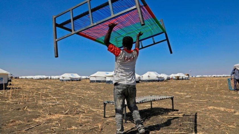 An Ethiopian refugee, who fled the Tigray conflict, carries a bed upon his arrival at the Tenedba camp in Mafaza, eastern Sudan on January 8, 2021, after being transported from the reception center.
