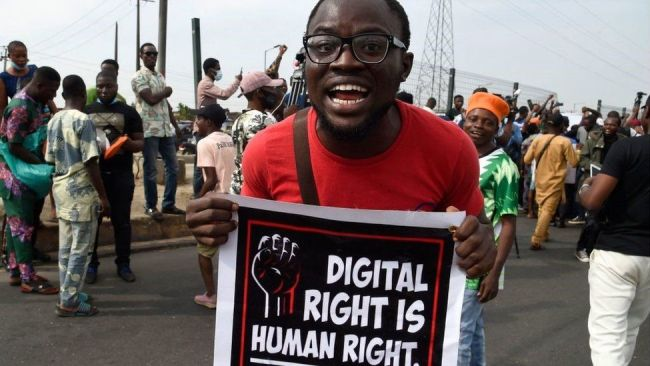A man carries a banner during a demonstration at Ojota in Lagos on June 12, 2021, as Nigerian activists called for nationwide protests over what they criticise as bad governance and insecurity, as well as the recent ban of US social media platform Twitter by the government of President Muhammadu Buhari.