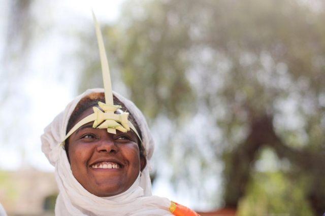A woman wearing a palm headdress smiles.
