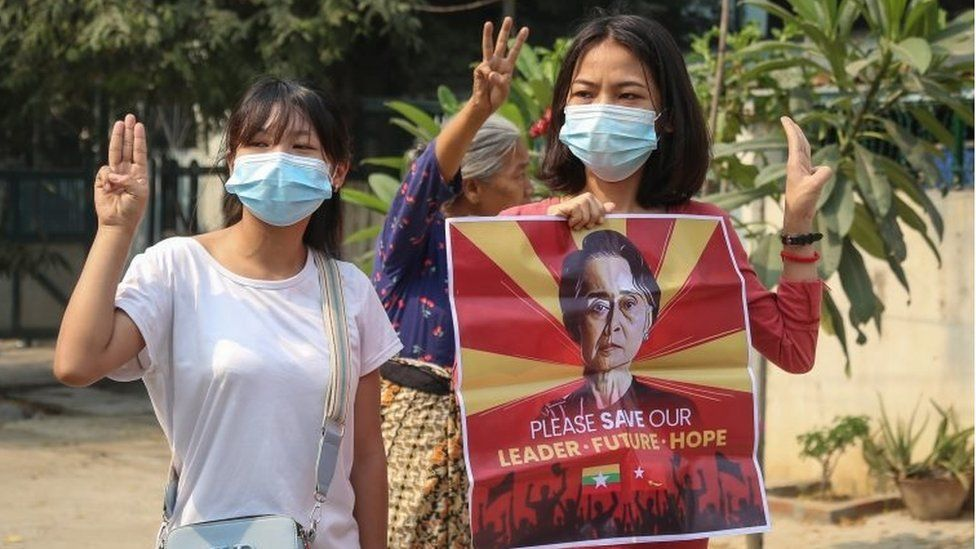 Demonstrators flash the three-finger salute while holding an image of detained leader Aung San Suu Kyi