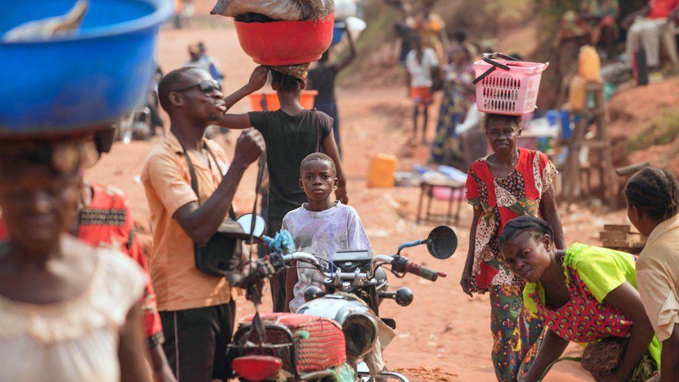 Vendedores y otros ciudadanos caminan en una calle del barrio 3Z, donde las confrontaciones entre la milicia de Kamuina Nsapu y el ejército son frecuentes en Tshikapa.