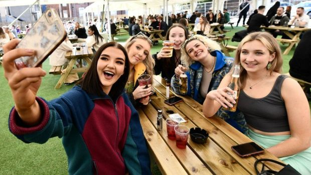 Young women enjoying drinks at an outdoor bar in Belfast