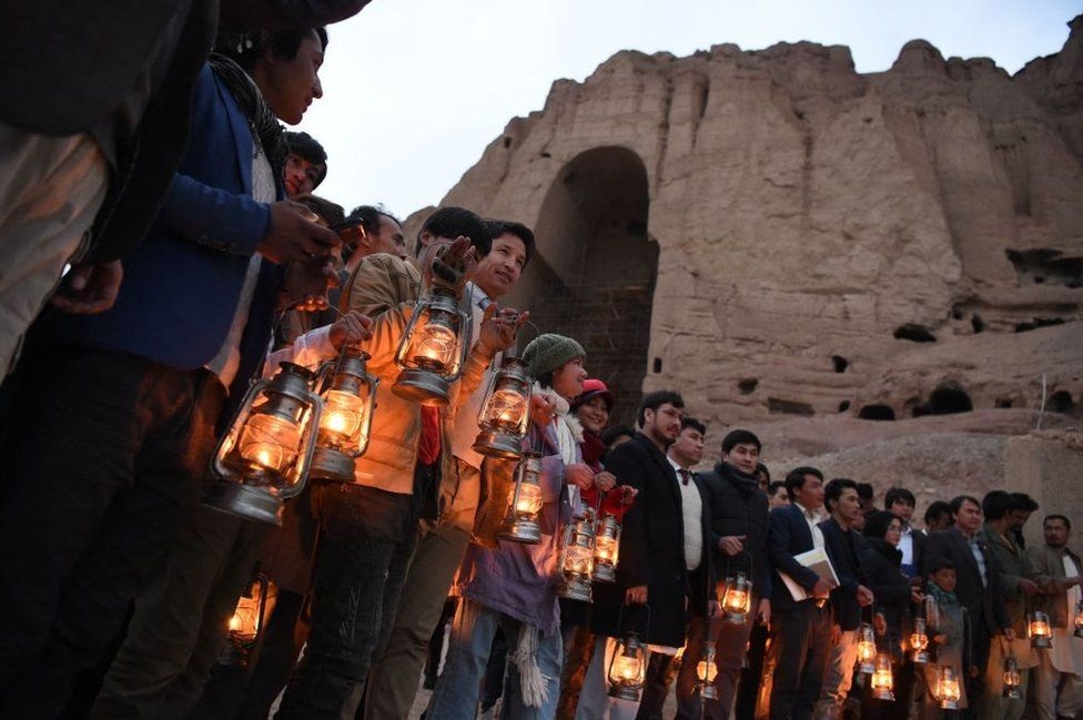 People holding lanterns stand beside the cliff