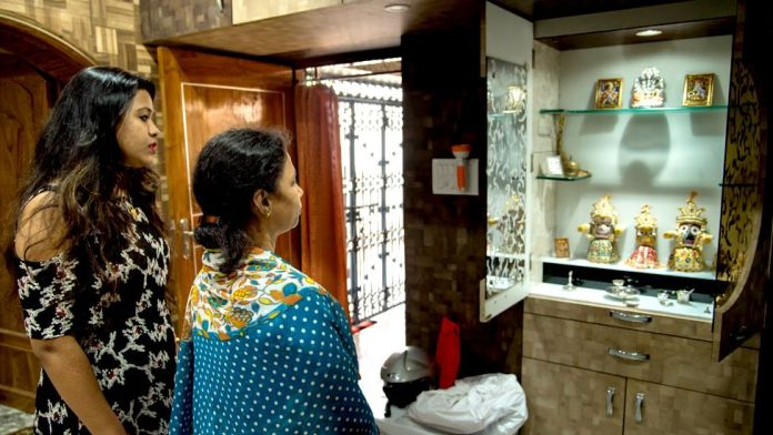 Bhagyashree and her mother-in-law look at a shrine in their home