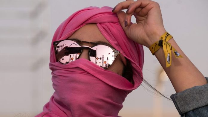 A woman in a pink head scarf with reflective sunglasses dances at the Dunes Electronique music festival in Ong Jmal, Tunisia - Saturday 16 November 2019