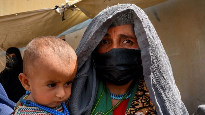 In this picture taken on March 28, 2021, Farzana, who fled her village in Helmand province when it was taken over by the Taliban, waits to see a doctor at a mobile clinic for women and children set up at the residence of a local elder in Yarmuhamad village, near Lashkar Gah in Helmand province.