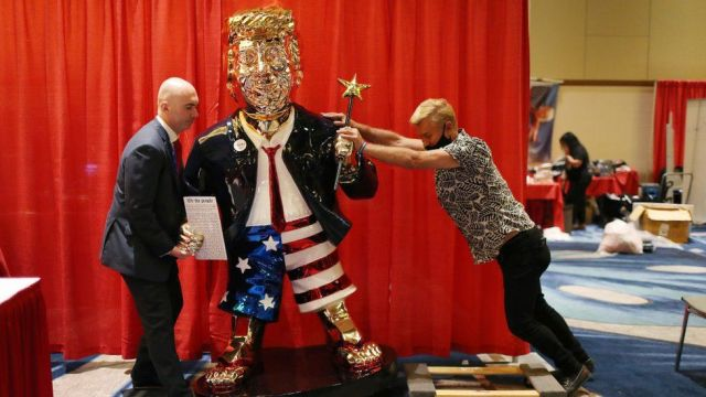 A golden statue of Donald Trump is seen being moved into CPAC conference