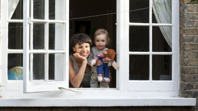 Woman and toddler looking out of an open window