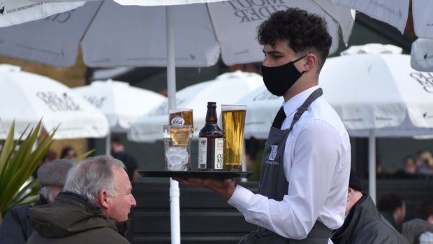 Barman delivering a pint outside in facemask