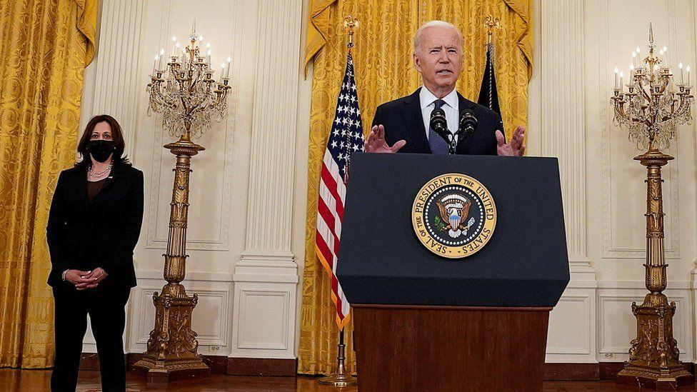 US President Joe Biden speaks, watched by Vice-President Kamala Harris