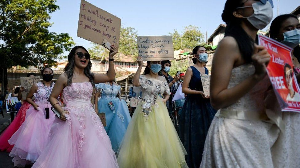 Myanmar women in wedding gowns holds up placards during a demonstration