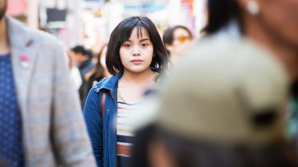 Mulher japonesa caminhando entre a multidão