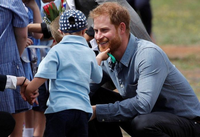 A young boy stroking Prince Harry's beard