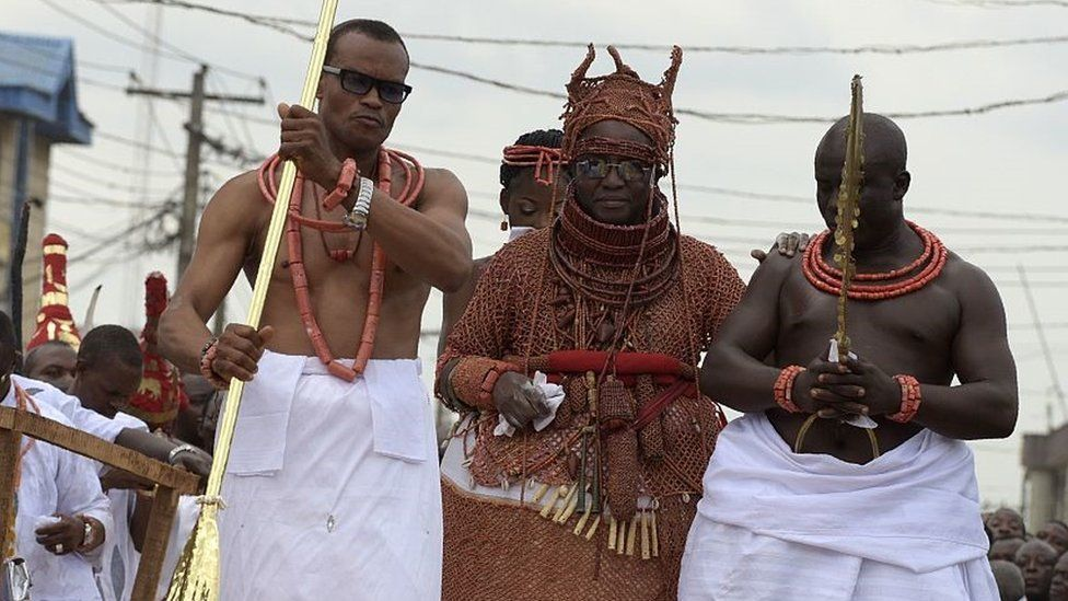 Newly crowned 40th Oba, or king, of the Benin kingdom, Oba Ewuare II (C), walks on a wooden bridge assisted by palace aides to perform the rite during his coronation in Benin City, midwest Nigeria, on October 20, 2016