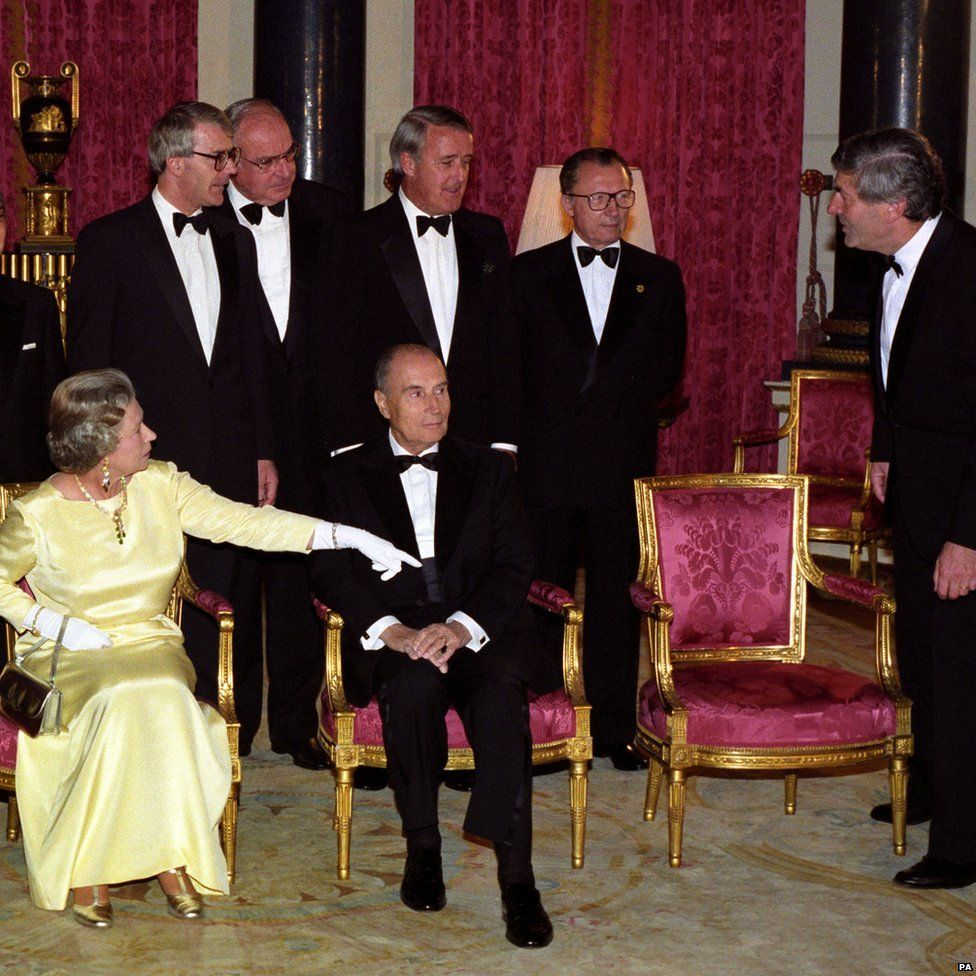 Queen Elizabeth II gesturing to Ruud Lubbers, Prime Minister of the Netherlands and President of the EC Council of Ministers, to sit on an empty chair after the Duke of Edinburgh was absent, as the leaders of the G7 Summit countries gathered for a pre-dinner photocall in the Music Room at Buckingham Palace, London