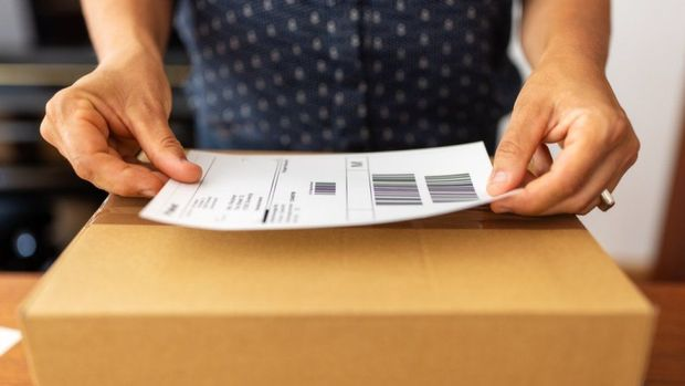 Woman online business owner prepares a package for shipping (file photo)