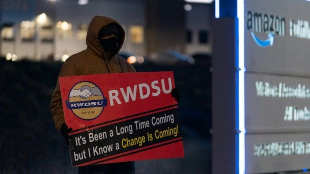 man with RWDSU sign outside warehouse in Alabama