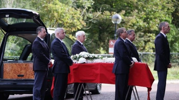 Pallbearers wait to carry the coffin of Roger Hunt