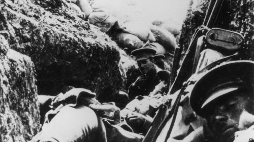 Soldiers wait in a trench