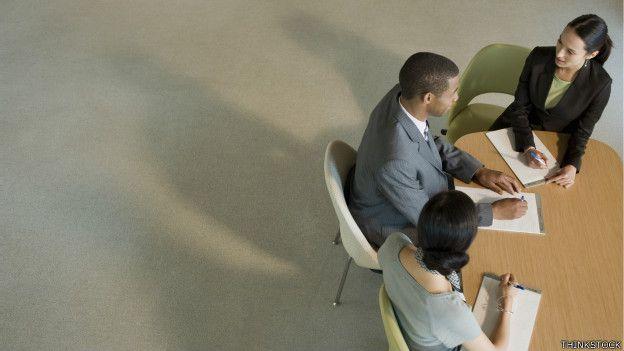 Tres personas en una mesa de trabajo