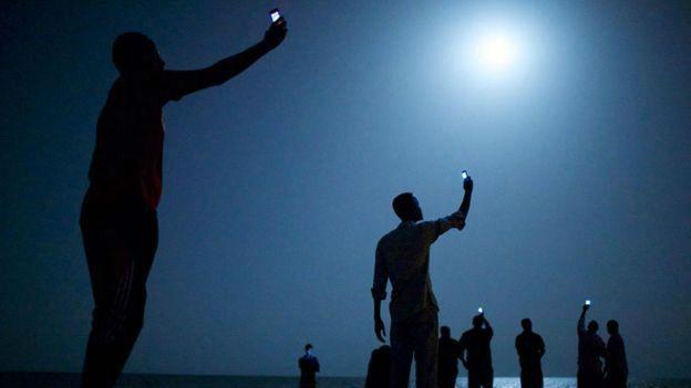 Inmigrantes intentan captar señal para sus teléfonos celulares