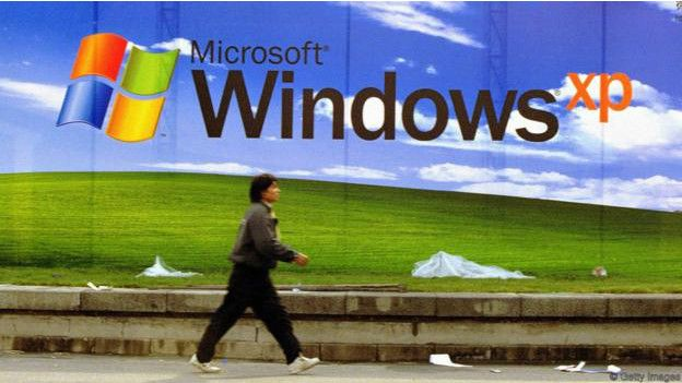 Una persona caminando frente a un poster de Windows XP
