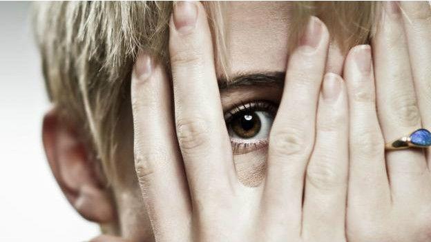 Una persona cubriéndose el rostro